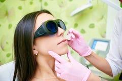 Le cosmetologist de docteur conduit la procédure de l'épilation de laser du corps d'une fille Épilation de laser cosmologie images stock