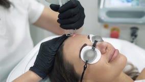 Le cosmetologist de docteur dans une robe de chambre et des gants exécute des procédures de laser sur le visage d'une fin femelle banque de vidéos