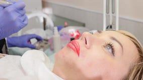 Le cosmetologist de docteur fait la procédure du maquillage permanent pour les lèvres femelles de client Mouvement lent clips vidéos