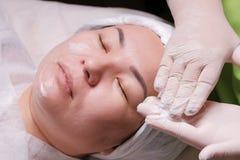 Le cosmetologist de main préparent la crème pour l'application au visage d'une fille asiatique La femme orientale se trouve sur l photo libre de droits