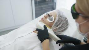 Le cosmetologist de mouvement lent fait la procédure de fille pour hydrater la peau du visage avec le dispositif spécial clips vidéos
