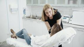 Le Cosmetologist examine le visage du patient avant procédure Jeune fille à la réception à l'esthéticien banque de vidéos