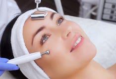 Le cosmetologist fait à l'appareil une procédure de la thérapie de Microcurrent d'un beau, jeune femme dans un salon de beauté photo libre de droits