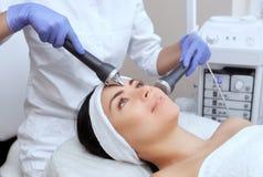 Le cosmetologist fait à la procédure un nettoyage ultrasonique de la peau faciale photos libres de droits