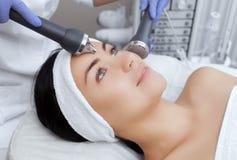 Le cosmetologist fait à la procédure un nettoyage ultrasonique de la peau faciale d'un beau, jeune femme dans un salon de beauté images libres de droits