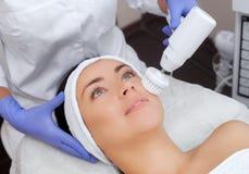Le cosmetologist fait la procédure d'appareil du nettoyage de visage de matériel avec une brosse tournante molle images stock