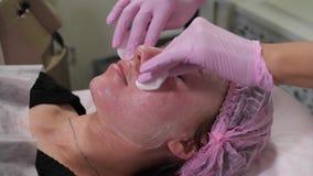 Le Cosmetologist met un masque sur le visage banque de vidéos