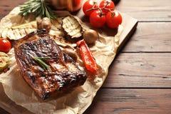 Le costole arrostite col barbecue deliziose sono servito con le verdure sulla tavola di legno fotografie stock