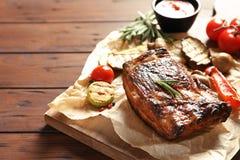 Le costole arrostite col barbecue deliziose sono servito con le verdure sulla tavola di legno immagine stock libera da diritti