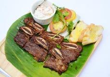 Le costole di carne di maiale tagliate arrostite con pane ed i pomodori sulla banana coprono di foglie fotografia stock