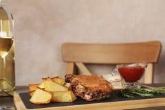 Le costole fritte sono servito con il contorno, la salsa ed il vino sulla tavola, spazio per testo fotografia stock