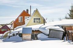 Le costruzioni del paese portate da neve Immagine Stock