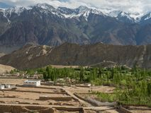Le costruzioni dell'argilla in un villaggio di alta montagna in Himalaya sono fra le gamme di alta montagna sotto il cielo nuvolo Fotografia Stock