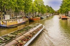 Le costruzioni e le barche di case vedono una barca turistica passare in un amsterd immagine stock
