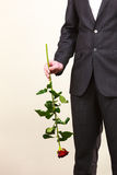 Le costume de port d'homme tient la fleur de rose de rouge Photographie stock