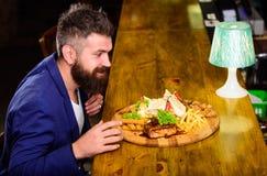 Le costume formel d'homme d'affaires se reposent au compteur de barre L'homme a re?u le repas avec les poissons frits de pomme de photos stock