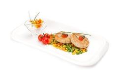 Le cotolette del pesce sono servito con il fagiolo dell'asparago e del mais Fotografia Stock
