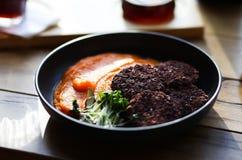 Le cotolette nere sane del riso del vegano sono servito con le carote arancio ingranano e microgreeens e caffè del decaffeinato A fotografia stock libera da diritti