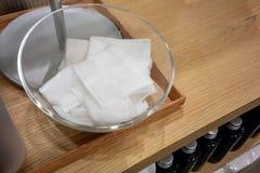 Le coton absorbant couvre dans le bol en verre clair sur la table en bois photos libres de droits