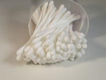 Le coton bourgeonne dans la boîte en plastique d'isolement sur le fond clair Photos stock