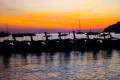 Le coucher du soleil à la plage et au bateau dans le style de silhouette photographie stock libre de droits