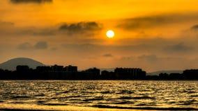 Le coucher du soleil à la ville et à l'océan Images libres de droits