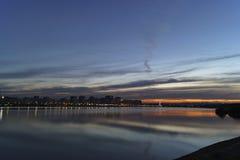 Le coucher du soleil égalisant au-dessus de la ville sur les banques de la rivière photographie stock libre de droits