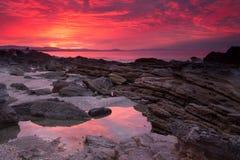 Le coucher du soleil étonnamment vif allume des piscines d'océan et de roche photo libre de droits