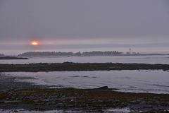Le coucher du soleil amorti comme soleil plonge dans le phare de Metis de banques de brouillard Images libres de droits