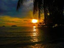 Le coucher du soleil ardent de lueur au-dessus d'une belle plage tropicale et l'océan arrosent Différentes couleurs des nuages et Photographie stock