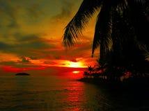 Le coucher du soleil ardent de lueur au-dessus d'une belle plage tropicale et l'océan arrosent Différentes couleurs des nuages et Photos stock