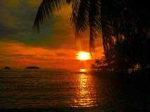 Le coucher du soleil ardent de lueur au-dessus d'une belle plage tropicale et l'océan arrosent Différentes couleurs des nuages et Photo stock