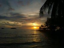 Le coucher du soleil ardent de lueur au-dessus d'une belle plage tropicale et l'océan arrosent Différentes couleurs des nuages et Image stock