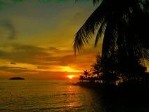 Le coucher du soleil ardent de lueur au-dessus d'une belle plage tropicale et l'océan arrosent Différentes couleurs des nuages et Photo libre de droits