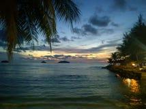 Le coucher du soleil ardent de lueur au-dessus d'une belle plage tropicale et l'océan arrosent Différentes couleurs des nuages et image libre de droits
