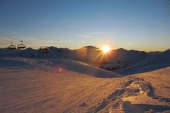 Le coucher du soleil au-dessus d'une neige a couvert la gamme de montagne alpine Photos libres de droits
