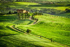 Le coucher du soleil au-dessus de la ferme en Toscane a placé sur une colline Images stock