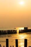 Le coucher du soleil au-dessus de la mer, et les poteaux électroniques sont drownig. Photographie stock