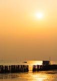 Le coucher du soleil au-dessus de la mer, et les poteaux électroniques sont drownig. Image libre de droits