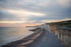 Le coucher du soleil au-dessus de sept soeurs marquent des falaises à la craie le Sussex est Angleterre R-U photos stock