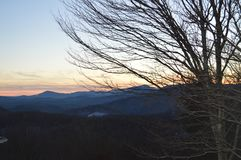 Le coucher du soleil au-dessus des montagnes et par les arbres Images stock