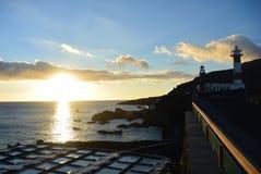 Le coucher du soleil au-dessus du phare et du sel met en place une La Palma Photo libre de droits