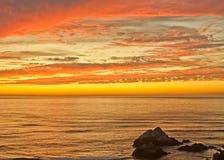 Le coucher du soleil au joint bascule la plage d'océan Photos stock