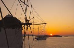 Le coucher du soleil aux moulins à vent de Mykonos et le yacht conduisent à vitesse normale Photo stock
