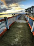 Le coucher du soleil commence au-dessus du dock de bord de mer à côté de l'hôtel iconique image libre de droits
