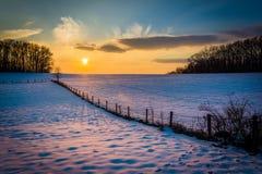 Le coucher du soleil d'hiver au-dessus d'une barrière et d'une neige a couvert le champ de ferme dans rural Images stock