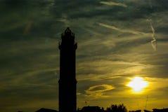 Le coucher du soleil dans la lagune ici est le phare sur l'île de Murano - Venise Photos stock