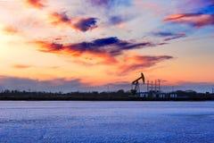 Le coucher du soleil de la machine de pompage d'huile Image stock