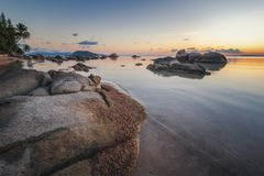 Le coucher du soleil de mer bascule la plage sur le fond de ciel bleu Lever de soleil de soirée de beauté Plage sablonneuse avec  photographie stock libre de droits