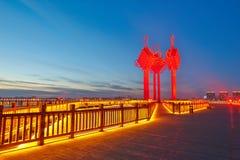 Le coucher du soleil de noeud chinois rouge et de ciel bleu Photographie stock